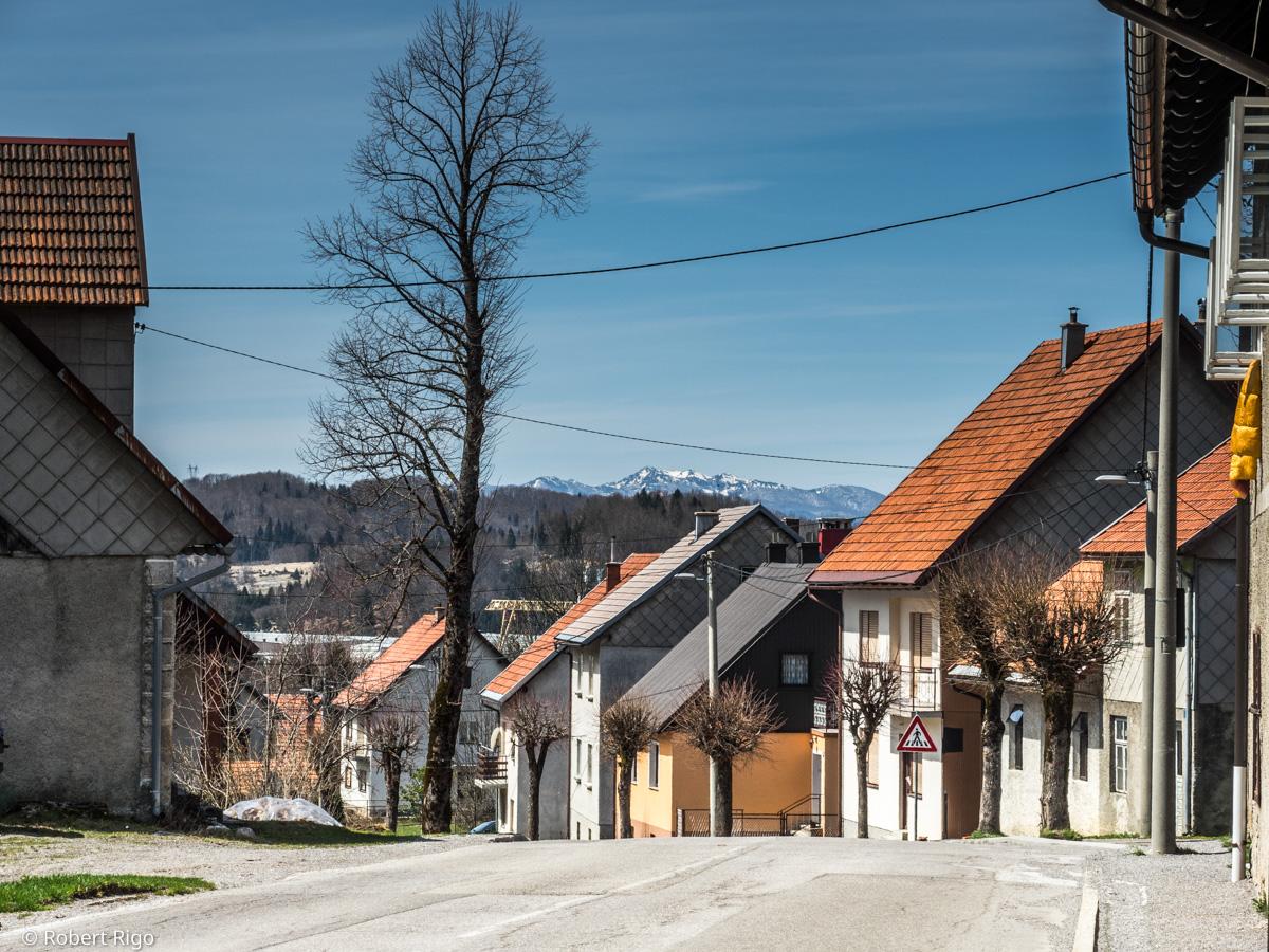 Pogled na ulaz u naselje Ravna Gora. Preko krovova kuća, u daljni, još uvijek možeš vidjeti snijeg na obroncima planina. Fotografirano 14.4.2018.