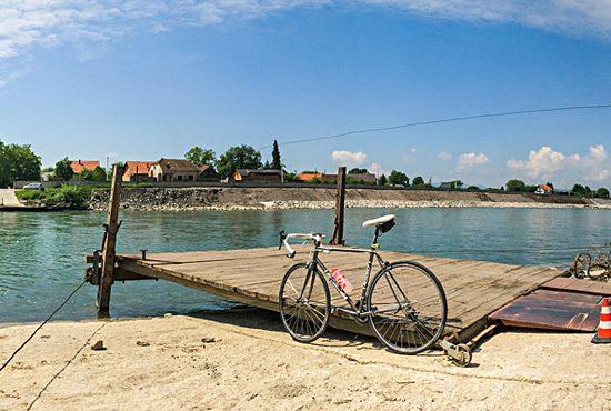 Pogleda na rijeku savu i pristanište skele. Bicikl je naslonjen na pristanište. Fotografirano: 13.5.2018.